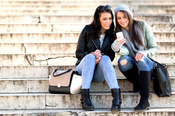Two young women sitting at the stairs and taking a selfie